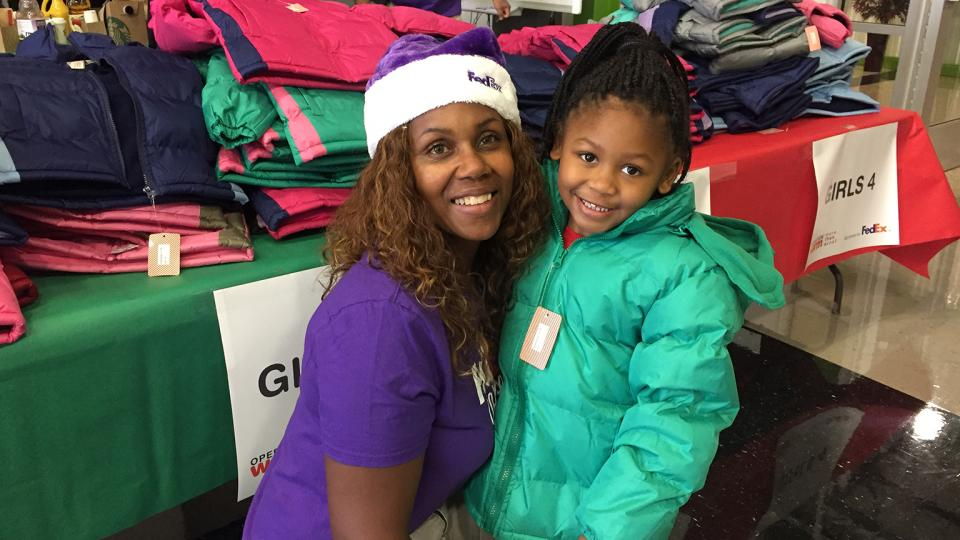 FedEx volunteer talking to child at Operation Warm event