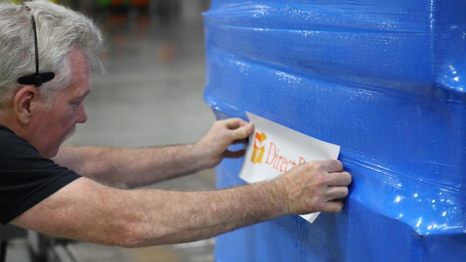 Man Adding Direct Relief Label to Package
