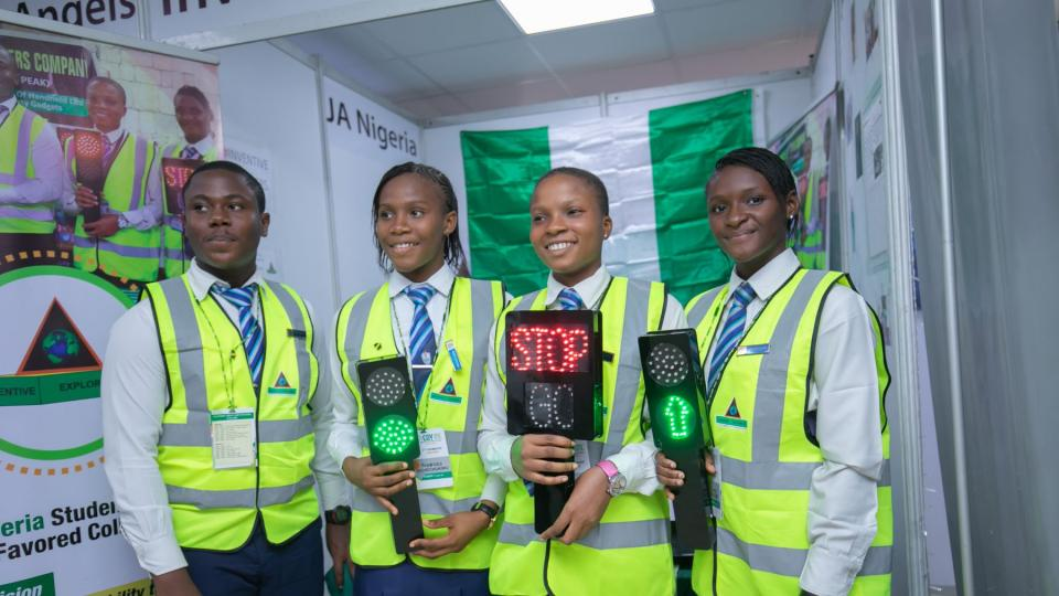 Four Junior Achievement participants standing with safety lights they invented