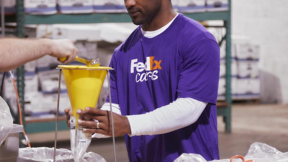 FedEx volunteer measuring food for a meal kit