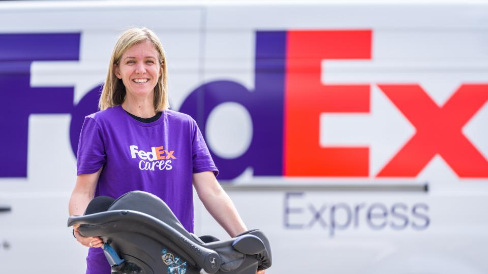 FedEx volunteer holding a car seat
