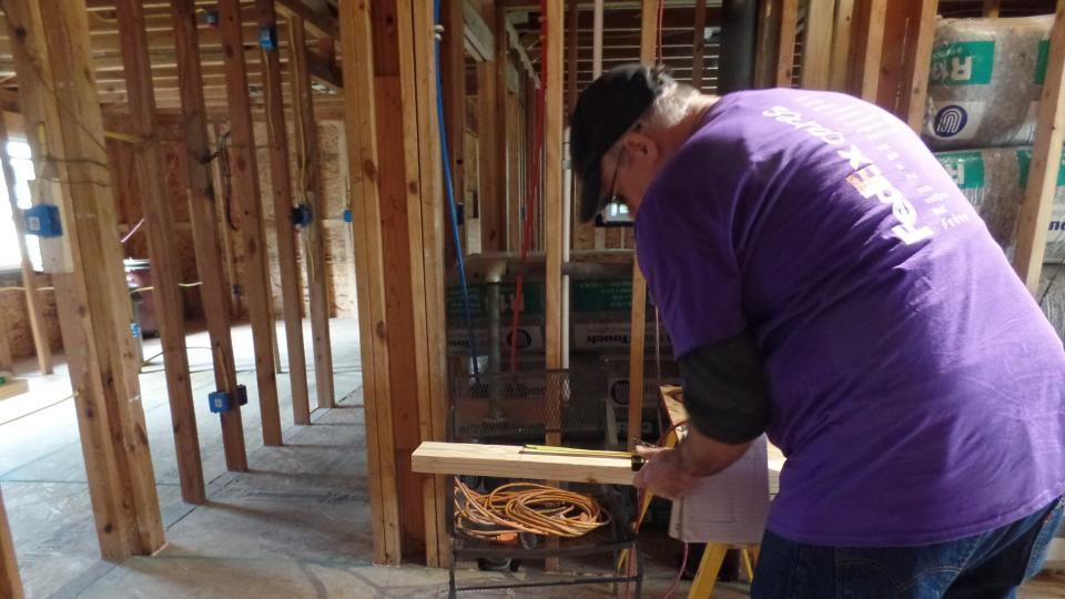 FedEx volunteer sawing a board to help build a house