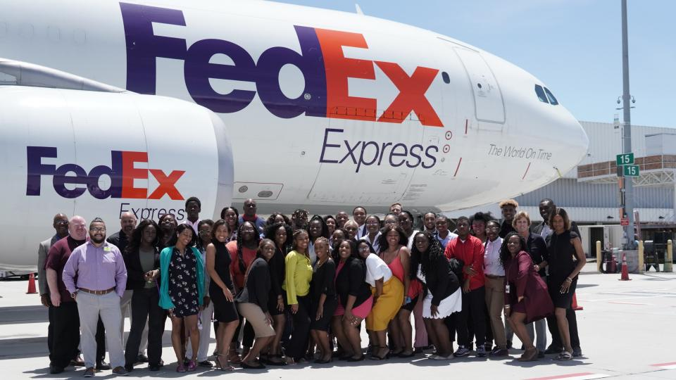 College scholars standing in front of a FedEx plane in Oakland