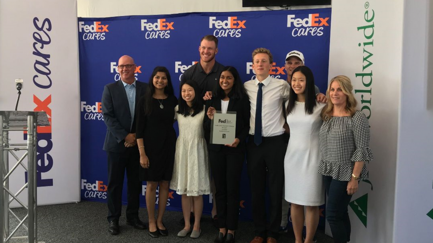 Junior Achievement winners standing in front of a FedEx Cares banner